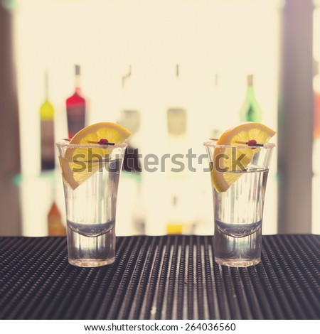 Two tequila shots with lemon on a bar ribber mat against highlighted glass wall. Shallow DOF, unusual light and toned - stock photo