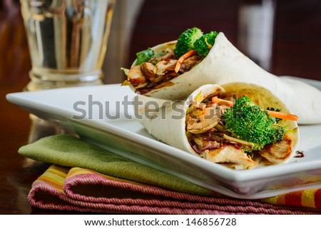 Two teriyaki chicken wraps with stir fried vegetables. - stock photo