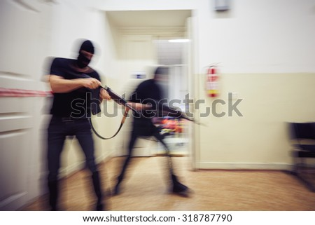 Two terrorists with rifles in the building - de focused - stock photo