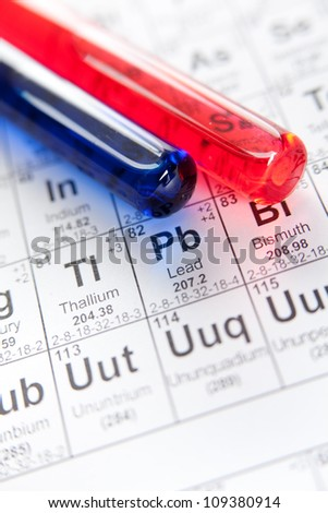Two test tubes with colored reagents lying on the periodic table, close-up shot - stock photo
