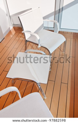 two textile chairs and table on balcony of cruise liner - stock photo