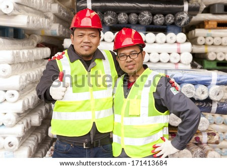 Two textile factory workers standing in  warehouse raw material fabrics with giving thumb up - stock photo