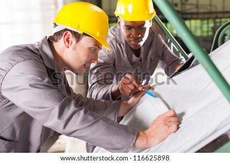 two textile workers checking fabrics quality on QC table - stock photo