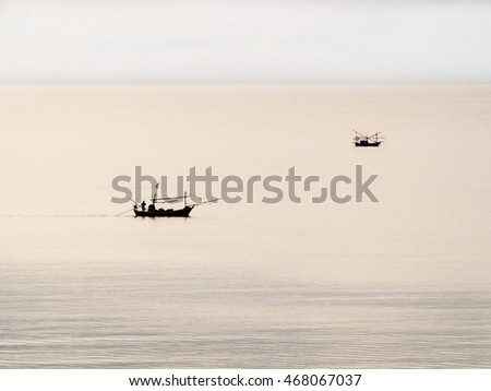 Two thai fisherman boat in the calm cloudy evening sea