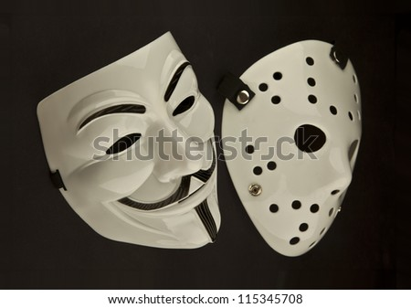 Two theatrical looking white masks on a black background. - stock photo