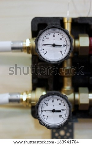 Two thermostats in home heating system - stock photo