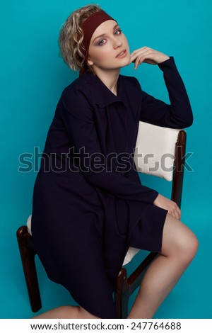 Two-third length fashion portrait of girl with lilac smoky eyes and natural lipstick, soft curls, bardic headband and severe dark coat seating half-turned on white leather chair on blue background - stock photo