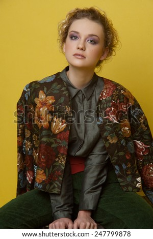 Two-third length fashion portrait of girl with lilac smoky eyes and natural lipstick. Wears casual grey blouse, moss green velvet trousers and dark jacket with big flowers on yellow background. - stock photo