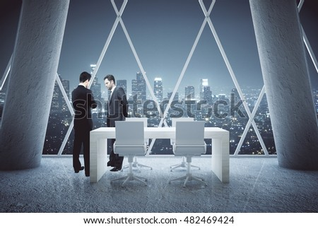 Two thoughtful businessmen standing in conference room interior with small table, concrete columns and night city view. 3D Rendering