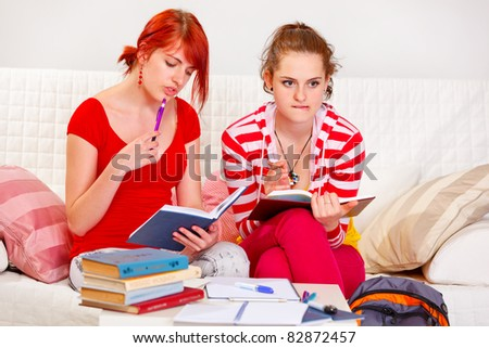 Two thoughtful girlfriends studying at living room - stock photo