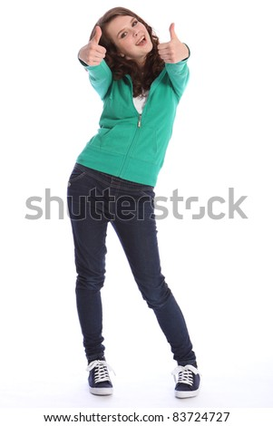 Two thumbs up for big success by happy pretty teenager school girl with long brown hair. She is wearing dark blue jeans and a green sweater.