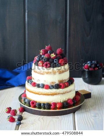 Two tiered white semi naked cake with fresh berries for a wedding or a party