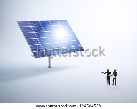 Two tiny engineers building a photovoltaic power plant - solar energy - stock photo