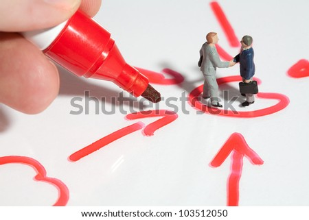 Two tiny miniature businessmen giving a business handshake sealing the deal standing in a schematic handrawn diagram of converging arrows with fingers holding a red marker pen for scale comparison - stock photo