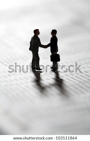 Two tiny miniature figurines of businessman standing in silhouette on a statistical document sealing a business transaction with a handshake - stock photo
