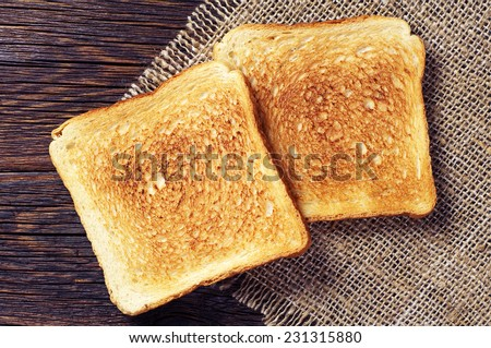 Two toast bread on wooden background closeup. Top view - stock photo