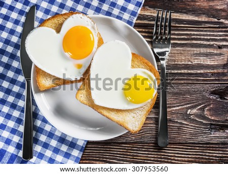 Two toast with scrambled eggs in the shape of a heart on a plate - stock photo