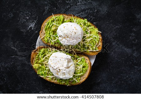 Two toasts with mashed avocado, cheese and poached egg on dark textured backdrop, top view. Healthy breakfast or snack - stock photo