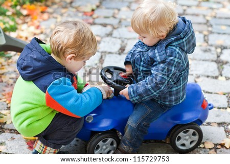 Two toddler boys playing with car in autumn park