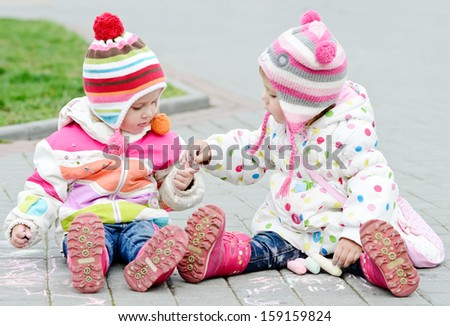 two toddler girls are playing and  drawing with chalk