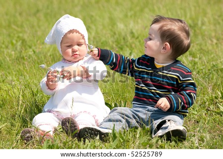 Two toddlers are sitting on the grass