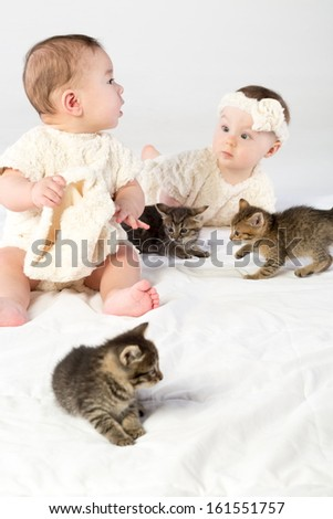Two toddlers dressed in white fur plays with little kittens