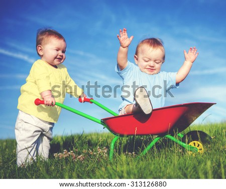 Two Toddlers Playing Together Outdoors Concept - stock photo