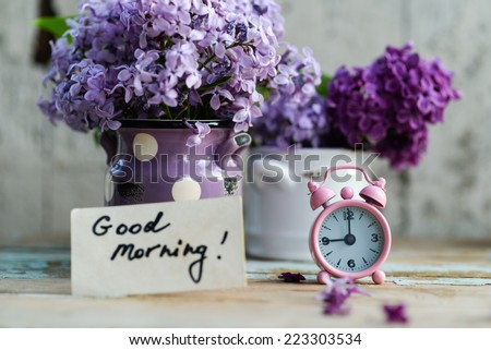 Two tone Lilac flowers in a ceramic pots white and purple, with pink vintage tiny alarm clock and a Good Morning note on a shabby wooden surface - stock photo