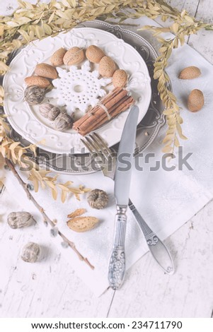 Two tone plates white and grey in a vintage style, served for Christmas dinner with vintage cutlery and white napkin on a shabby white table with spices and other decorations. - stock photo