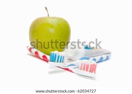 Two toothbrushes and apple in the background - stock photo