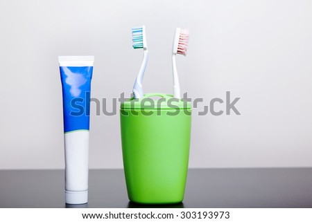Two toothbrushes and toothpaste stand on a table in a glass.