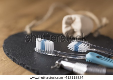 Two toothbrushes with a dentists drill and mold of tooth lying on a black mat with focus to the bristles of one brush in a dental and healthcare concept - stock photo