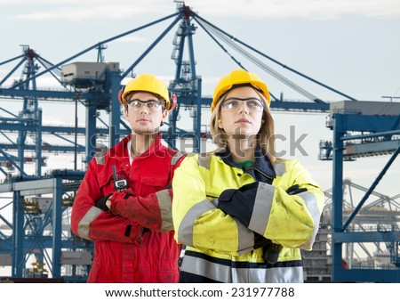 Two tough looking dockers in safety clothing posing in front of a huge container terminal - stock photo