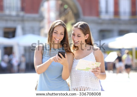 Two tourist friends consulting an online guide on a smart phone in the street