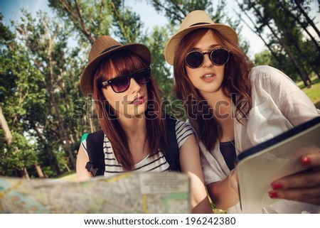 Two Tourist Girls In Nature Browsing Map Using Digital Tablet - stock photo