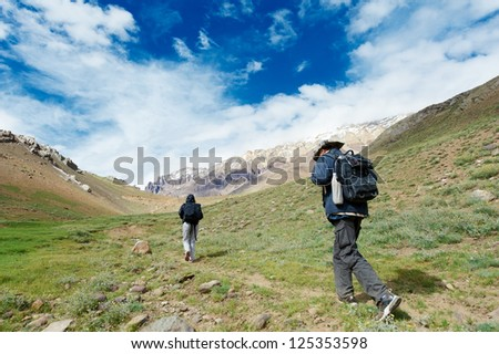 Two tourist traveller hiker walking in india Himalayas mountains