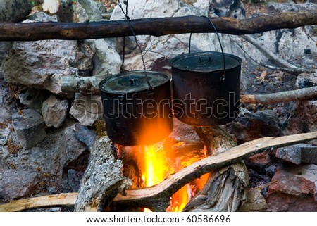 two tourists kettles on campfire - stock photo