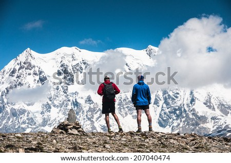 two tourists on the top of the mountain - stock photo