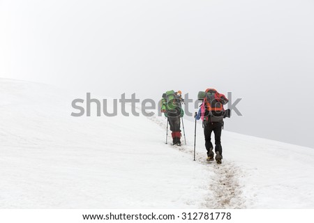 Two tourists walking on snow
