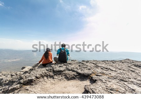 Two tourists with backpacks resting on top of a mountain