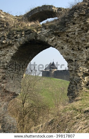 Two towers of ancient castle through old arch