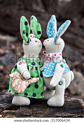 Two toy bunny in love on an old wooden surface - stock photo