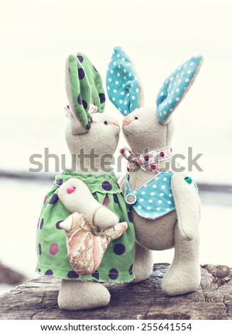 Two toy bunny in love on an old wooden surface. toned photo - stock photo
