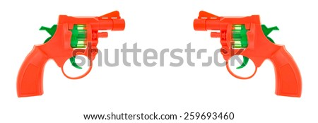 Two toy cap gun aiming at each other on a white background. - stock photo