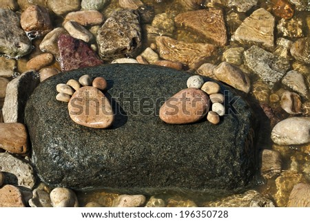 two trace feet made of a pebble stone on the sea wave backdrop