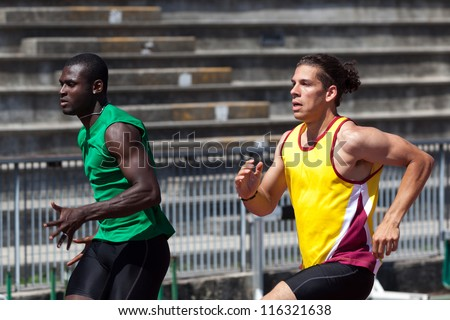 Two Track and Field Athletes Running - stock photo