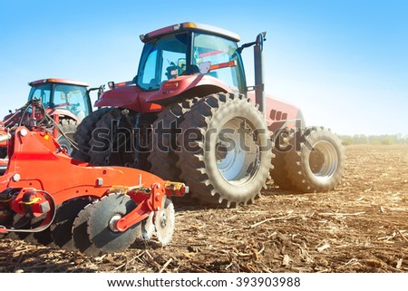 Two tractors in a field on a bright sunny day - stock photo