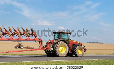 two tractors with  ploughs - one on the road, another - in field - stock photo