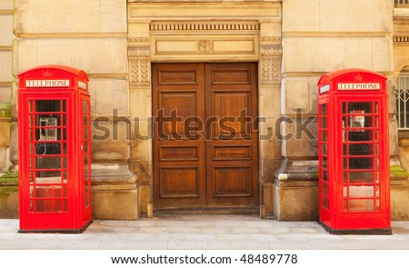 Two traditional British red phone boxes in front of a stone building - stock photo