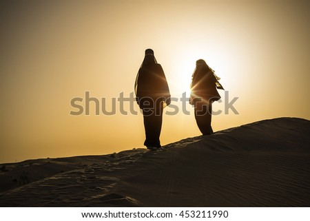 two traditional clothed women standing on a sand dune in the evening sun